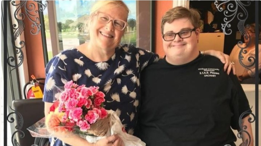 Marget and her son Zach. Marget is a woman with white skin and blonde hair. She is holding a bouquet of flowers. She has her arm around her son Mark - young adults with white skin and brown hair.